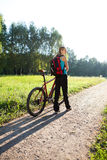 Woman cyclist with bike in spring park. Woman cyclist with bike on bicycle walk in spring sunny park Royalty Free Stock Photography