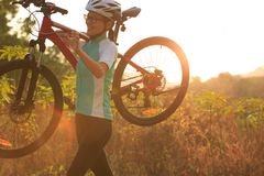 Woman cyclist carrying her mountain bike Stock Photography