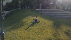 Woman cyclist lying on green grass in park and using mobile phone