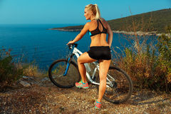 A woman cyclist on a mountain bike looking at the landscape of m Royalty Free Stock Images