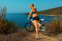 Woman cyclist on a mountain bike looking at the landscape of mou Royalty Free Stock Image