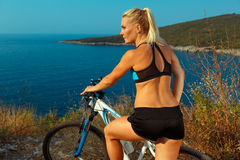Woman cyclist on a mountain bike looking at the landscape of mou Stock Photo