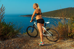 Woman cyclist on a mountain bike looking at the landscape of mou Stock Image