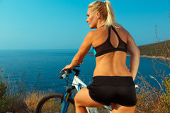 Woman cyclist on a mountain bike looking at the landscape of mou Stock Photos