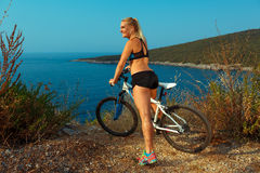 Woman cyclist on a mountain bike looking at the landscape of mou Stock Images