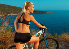 Woman cyclist on a mountain bike looking at the landscape of mountains and sea. Young woman cyclist on a mountain bike looking at the landscape of mountains and stock images