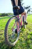 Woman the cyclist on mountain bike in park. Woman the cyclist on mountain bike in city park Royalty Free Stock Photo