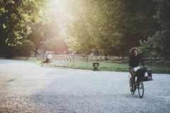 Woman cyclist in the park at sunset Stock Photo