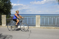 Woman cyclist passing a lake view Royalty Free Stock Photo