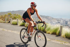 Woman cyclist practicing for triathlon competition Stock Photos