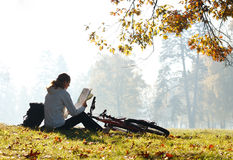 Woman cyclist with read the map Royalty Free Stock Images