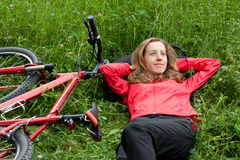Woman cyclist relaxes lying among the green grass Royalty Free Stock Images