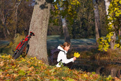 Woman cyclist relaxing in autumn park. Near the pond with yellow maple leaves in her hand Royalty Free Stock Photography