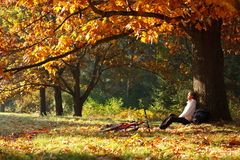 Woman cyclist relaxing in autumn park Stock Image