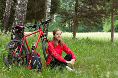 Woman cyclist relaxing among the green of nature Stock Photos