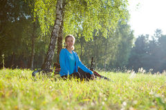 Woman cyclist relaxing in spring park. Young woman cyclist enjoying relaxation in spring sunny park sitting near a birch trunk Royalty Free Stock Image