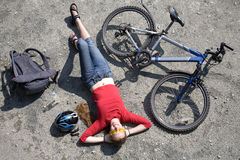 Woman  cyclist rest near bike. Woman  cyclist resting near bike in summertime Royalty Free Stock Image