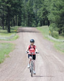 A Woman Cyclist Rides a Forest Road Royalty Free Stock Photos