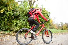 Woman cyclist riding a bike in autumn park Stock Photos
