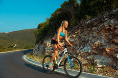 Woman cyclist riding a bike on a mountain road Stock Photos