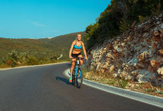 Woman cyclist riding a bike on a mountain road Stock Image