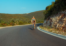 Woman cyclist riding a bike on a mountain road Royalty Free Stock Photography