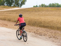 Woman Cyclist Riding On The Road Royalty Free Stock Images