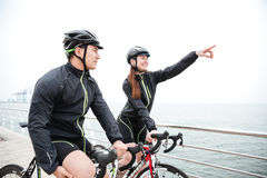 Woman cyclist showing finger on something to her boyfreind Stock Photo