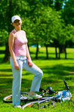 Woman cyclist stays near lying bike. Young woman biker on the bicycle stand in the park. She tiredly steps on bike and have a rest. It`s a hot summer Stock Photography