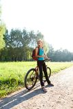 Woman cyclist on walking with bicycle in spring nature Stock Photo