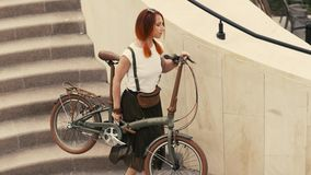 Woman cyclist walking down stairs and holding bicycle in arms. Woman bike city royalty free stock image