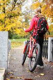 Woman Cyclist With Bike And Backpack In Autumn Park Royalty Free Stock Images