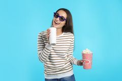 Woman with 3D glasses, popcorn and beverage during cinema show. On color background royalty free stock photography