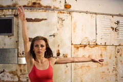 Woman in Dance Pose with Arms Out. A woman standing in a dance pose in front of a rusty background Stock Image