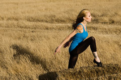 Woman in Dance Pose in a Field of Grass. A woman standing in a dance pose in a field of grass in the country Royalty Free Stock Photos