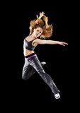 Woman dancer dancing modern dance, jump on a black Stock Photos