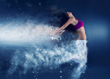 Woman dancer jumping. Young woman dancer jumping and decomposing in particles on blue background stock photo