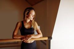 Woman dancer posing near barre in ballet studio. Beautiful woman dancer posing near barre in ballet studio Stock Photos
