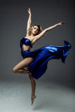 Woman dancer wearing blue skirt. Beautiful young woman dancer in blue top, long blue skirt dancing Stock Photo