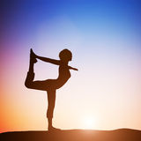 Woman in the dancer yoga pose meditating at sunset. Zen Stock Images