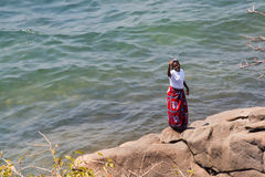 Woman dances at the beach at Lake Malawi. Royalty Free Stock Photography