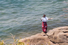 Woman dances at the beach at Lake Malawi. Royalty Free Stock Photos