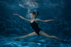 The woman dances at the bottom under water. Stock Photography