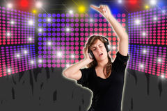 Woman Dancing. Using headphones with disco lights in the background Royalty Free Stock Image