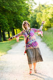 Woman dancing as she walks along path Royalty Free Stock Photos