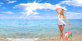 Woman dancing on the beach. With a beach bag Stock Images