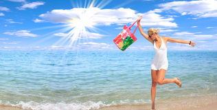 Woman dancing on the beach. With a beach bag Royalty Free Stock Image