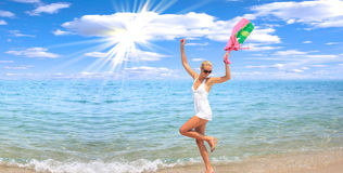 Woman dancing on the beach. With a beach bag Royalty Free Stock Images