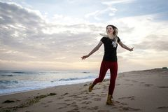Woman dancing at the beach during beautiful sunrise. Woman dancing at the beach during beautiful sunrise Stock Images