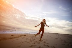 Woman dancing at the beach during beautiful sunrise. Woman dancing at the beach during beautiful sunrise Royalty Free Stock Photos